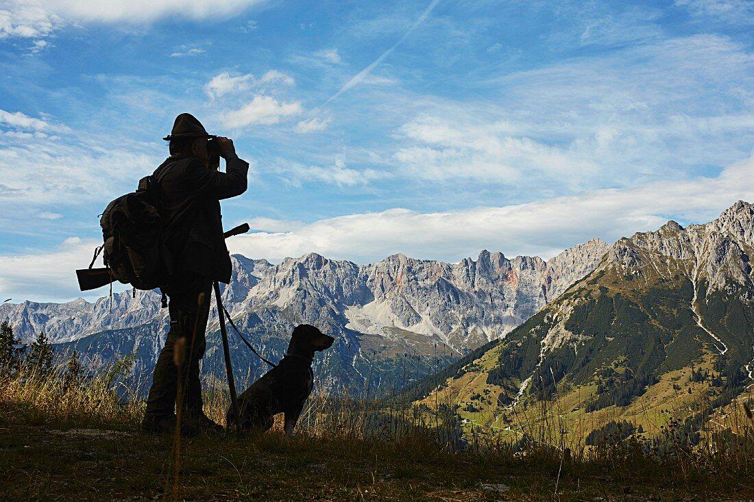 Jäger mit Jagdhund vor Bergkulisse