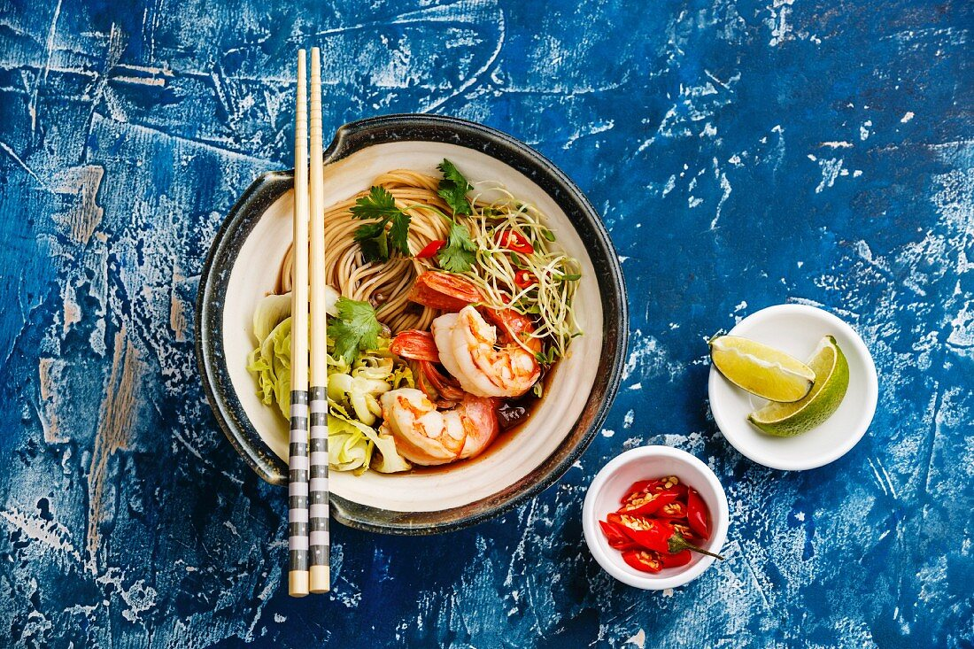 Asian Ramen noodles with Prawns and greens on blue background