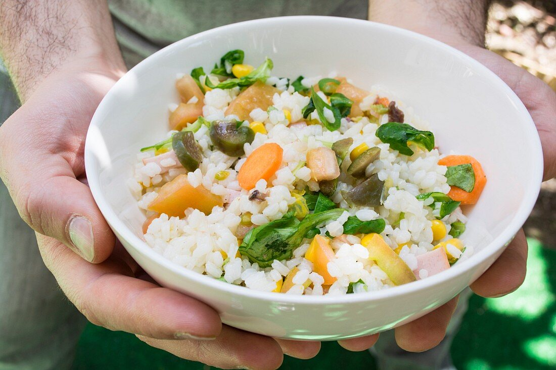 Hands holding a bowl of rice salad with tomatoes, basil, olive oil, olives, sweetcorn and carrots