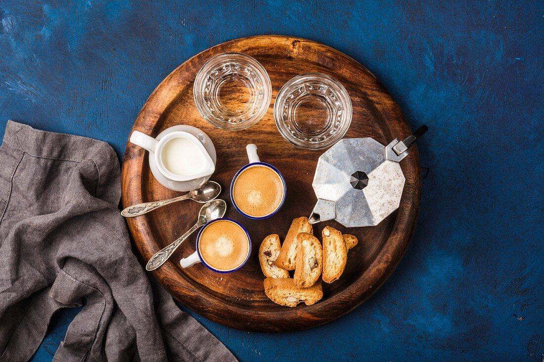 Espressokanne, Cantucci, zwei Tassen Espresso, Milch und Wassergläser auf Holztablett