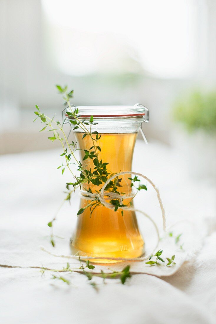 Home-made thyme syrup and sprigs of thyme