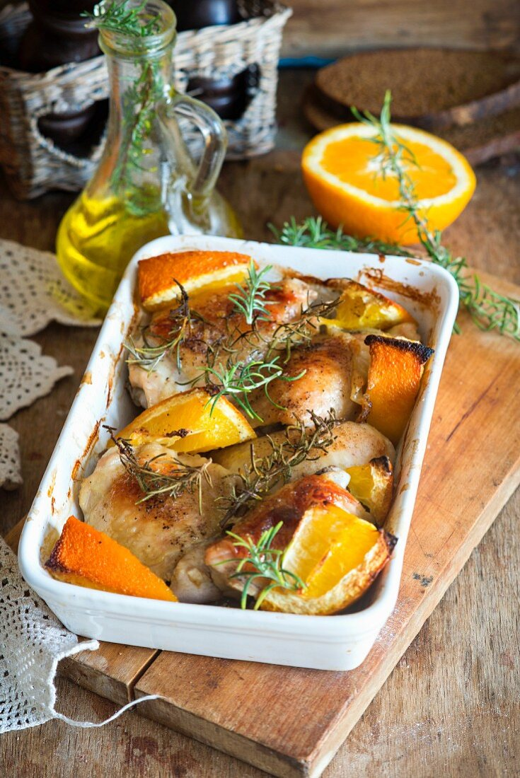 Roast chicken thighs with orange wedges and rosemary
