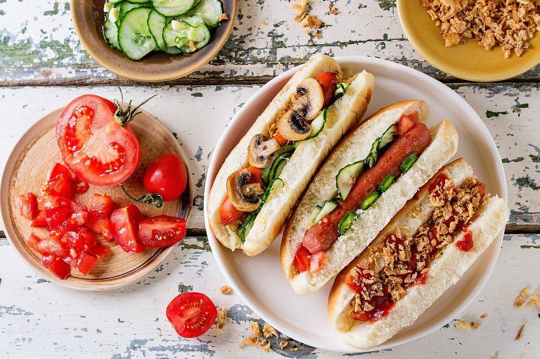 Selbst gemachte Hot Dogs mit gebratenen Zwiebeln, Tomaten und Gurken, serviert mit Zutaten