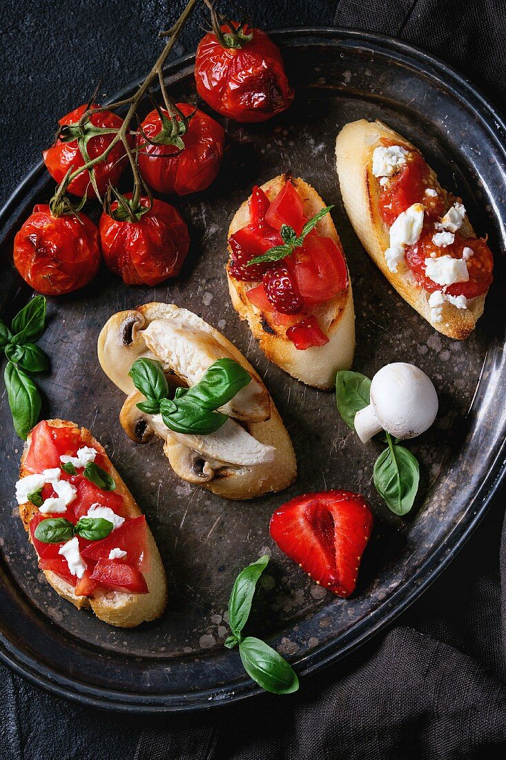 Assorted bruschetta with tomatoes, strawberries, feta cheese, chicken, mushrooms and basil on a vintage metal tray