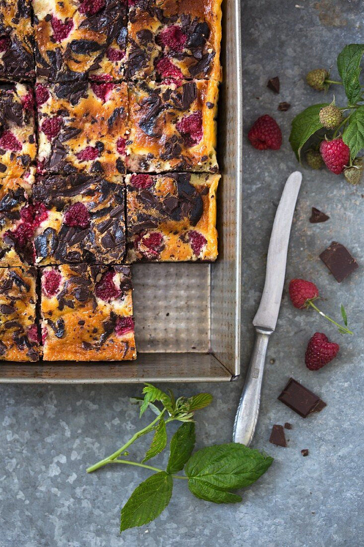 Cheesecake brownies with raspberries in a baking pan (seen from above)