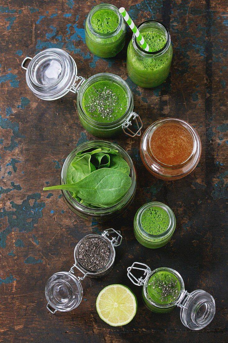 Spinat-Smoothie in Gläsern, serviert mit Spinatblättern, Chiasamen, Honig und Limette