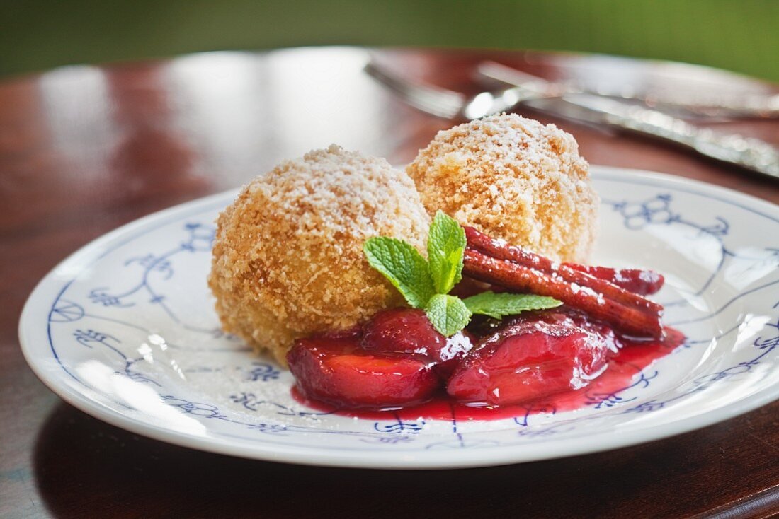 Damson dumplings with a cinnamon stick and mint