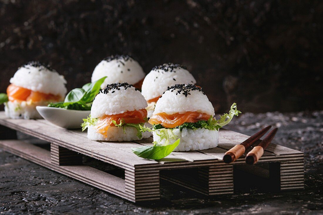 Mini rice sushi burgers with smoked salmon, green salad and sauces, black sesame served on wood pallet tray