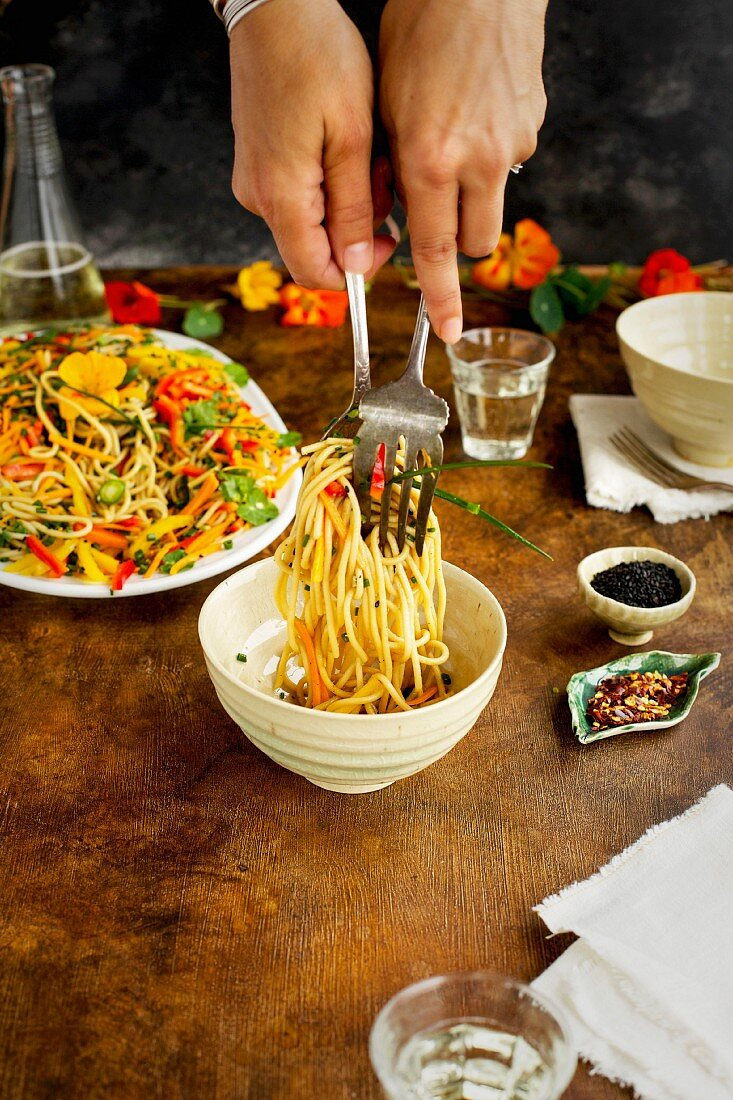 A woman is serving Asian Sesame Pasta Salad served with white wine