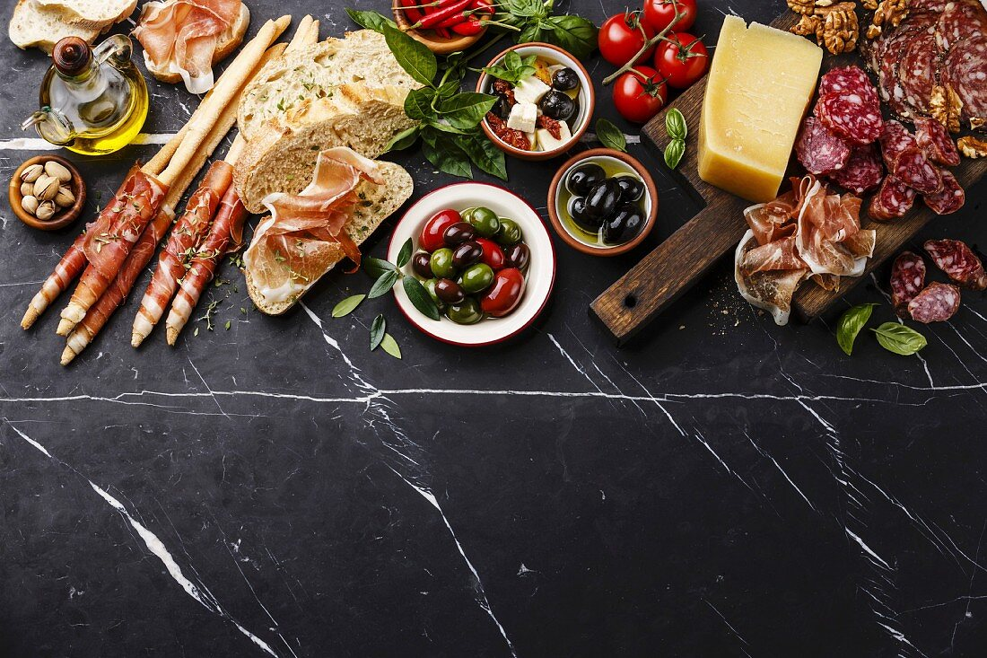 Italian snacks food with Ham, Sliced bread Ciabatta, Olives, Parmesan cheese, Grissini bread sticks, Feta cheese with dried tomatoes and Sausage on dark marble background