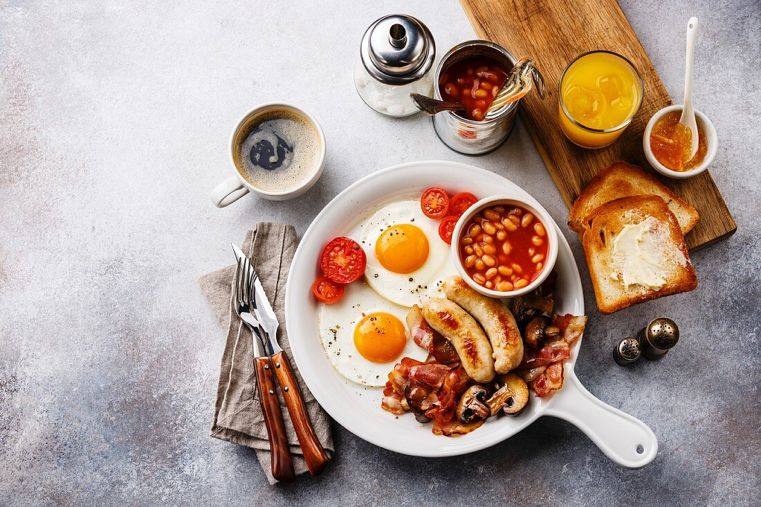 English breakfast in white pan with fried eggs, sausages, bacon, beans, toasts, orange fresh and coffee on white background