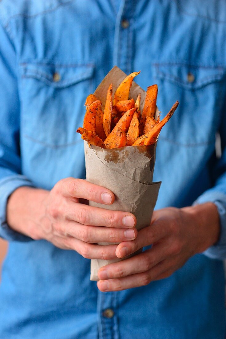 Man holds in his hands the fries of the sweet potato