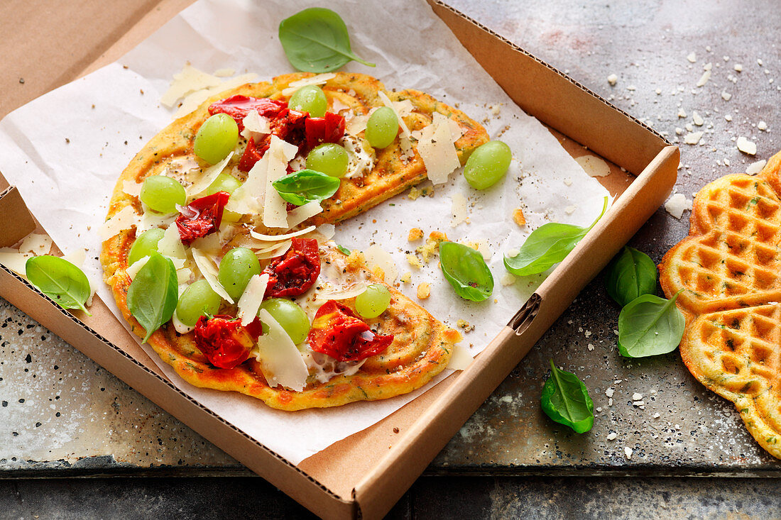 Vegetarian cheese waffles with grapes, cherry tomatoes and basil