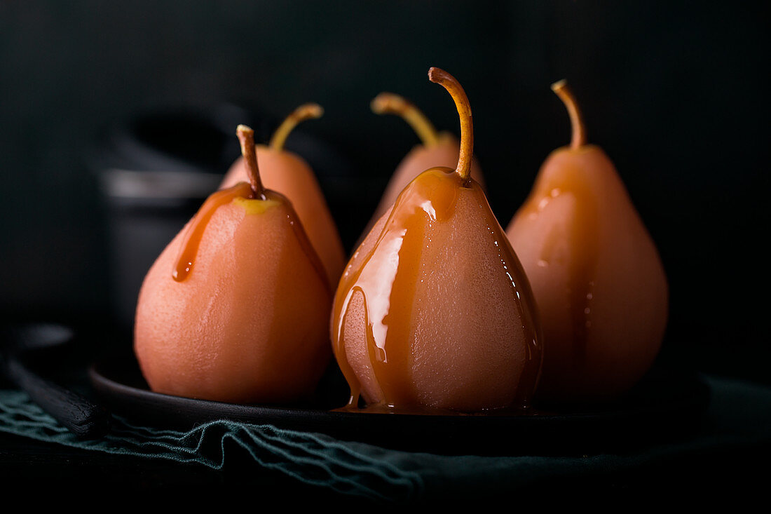 Pears cooked in red wine with caramel sauce for Christmas