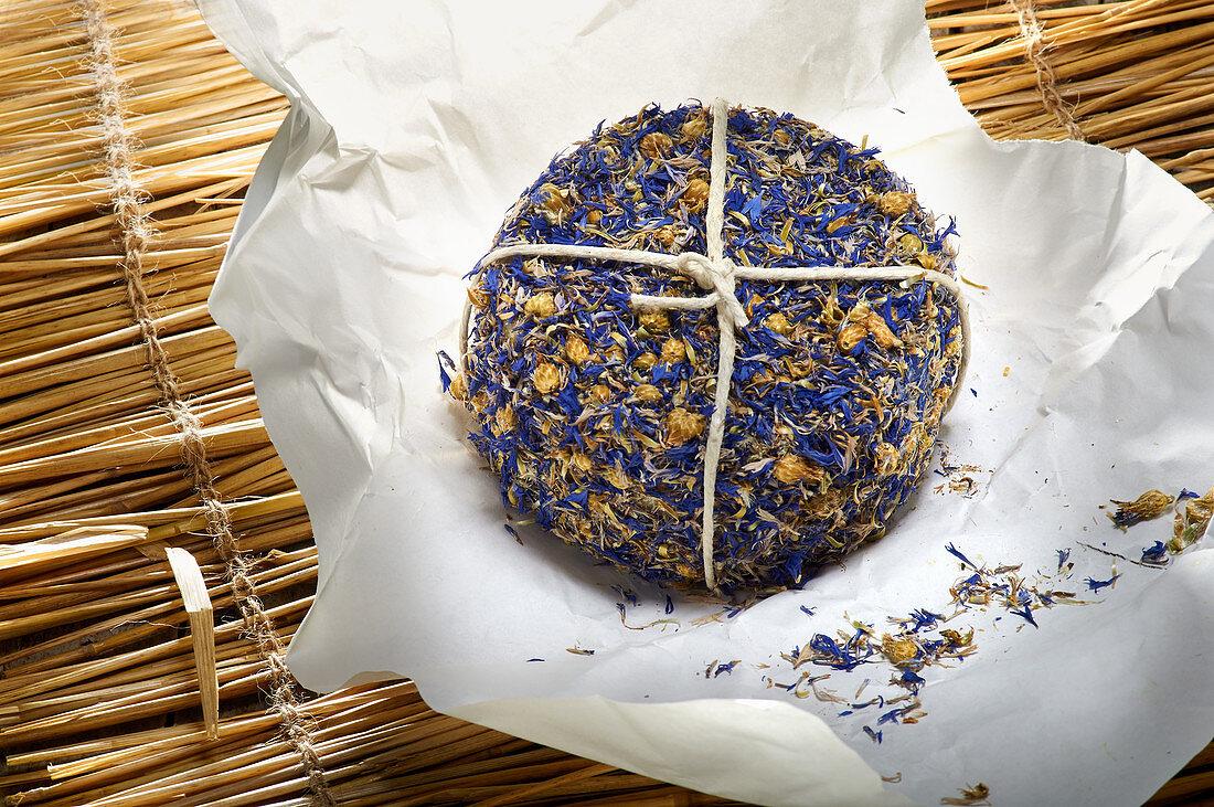 Cornflower-coated pecorino on a straw mat