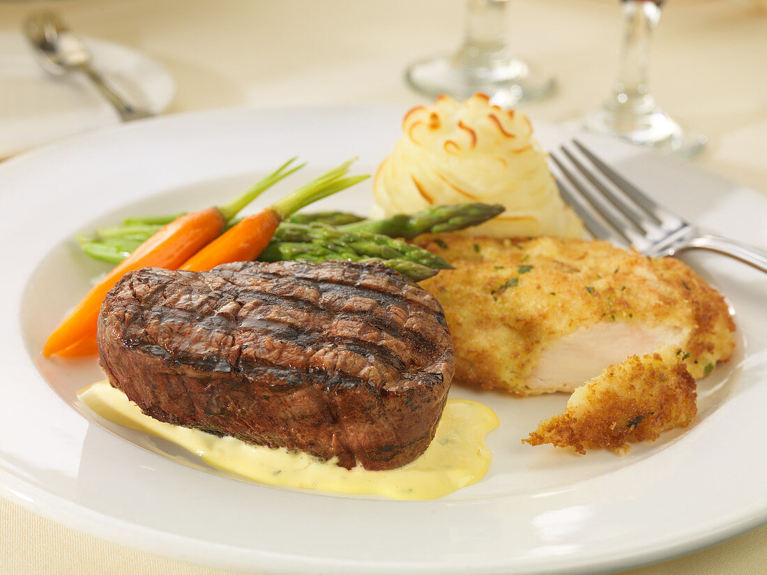 Steak and chicken schnitzel with vegetables and mashed potato