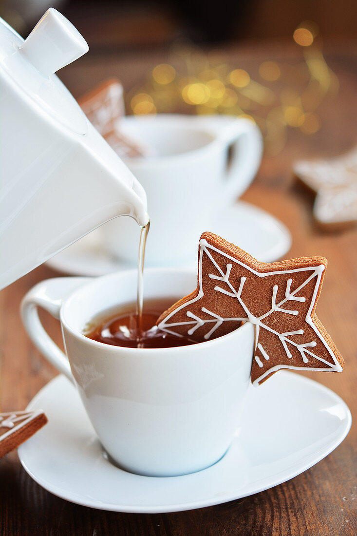 Tea being poured into a cup and a gingerbread heart biscuit