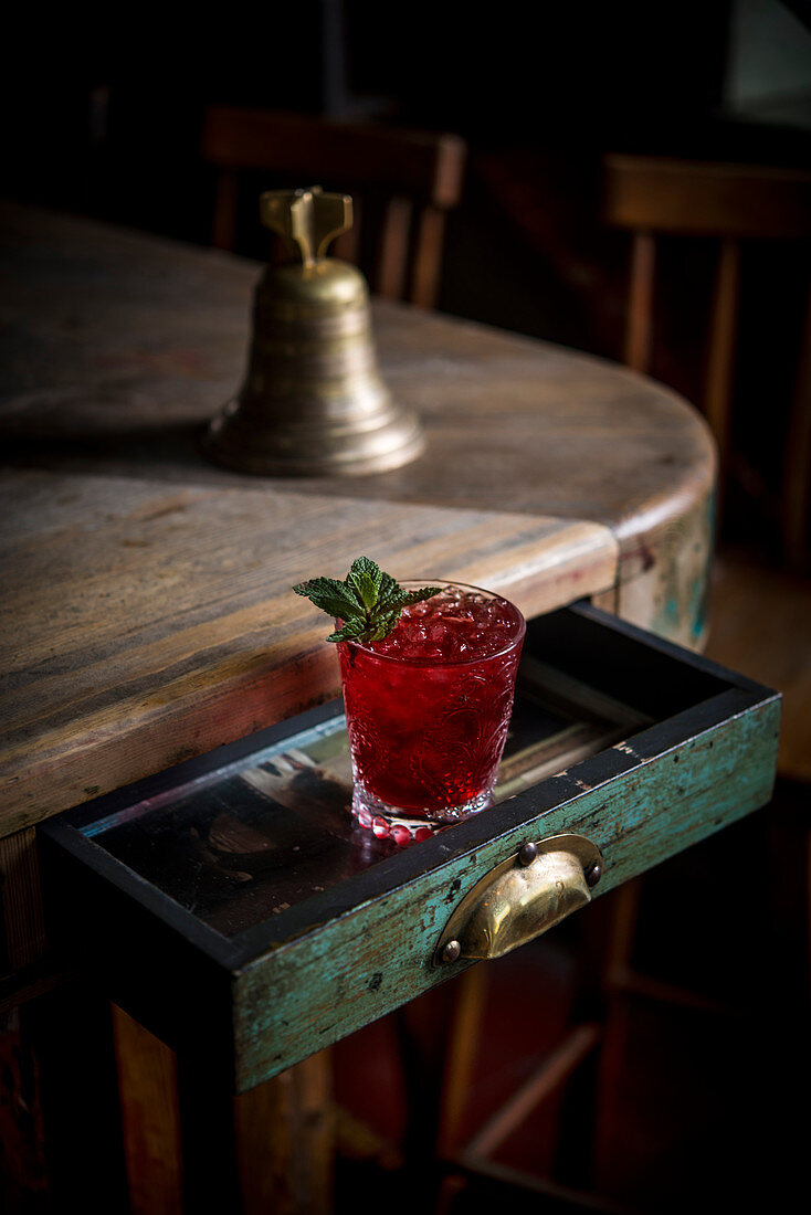 A red cocktail with ice cubes and mint leaves