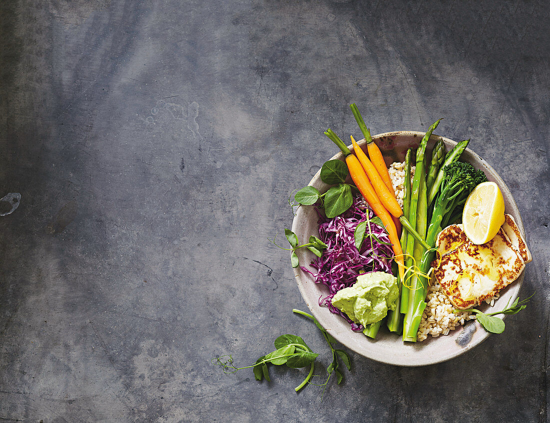 A veggie bowl with spring vegetables and haloumi