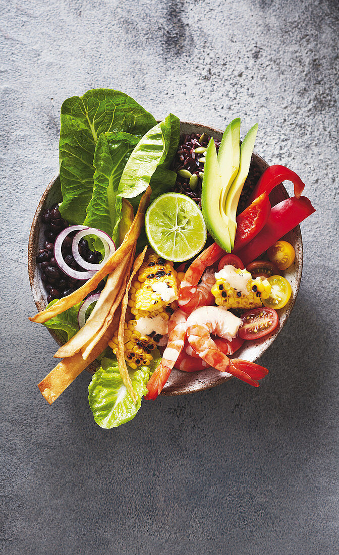 A taco bowl with prawns, rice, sweetcorn, beans and avocado