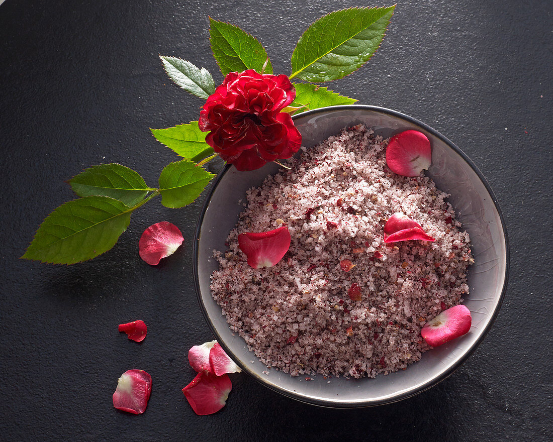 Rose petal salt with fresh petals in a ceramic bowl with a rose