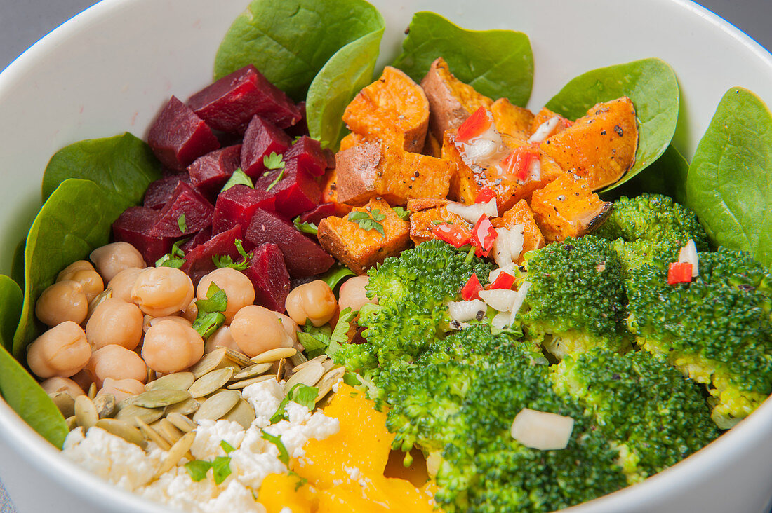 Buddha bowl with baby spinach, sweet potatoes, broccoli, mango, feta cheese, chickpeas and beetroot