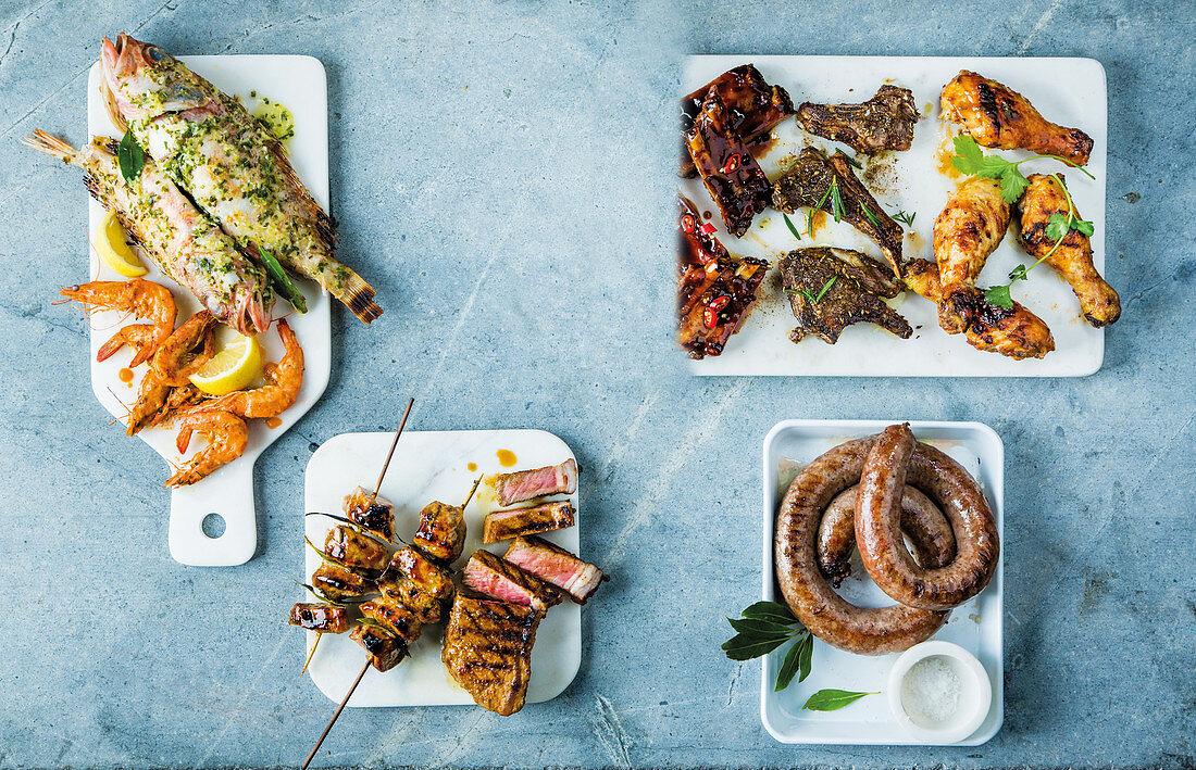 Various grilled dishes: pork, chicken, sausage, steak, fish, shrimp