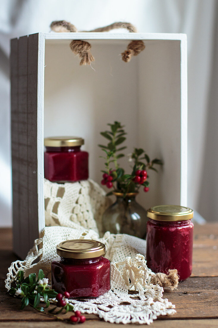 Three glasses of cranberry jam in a white wooden box