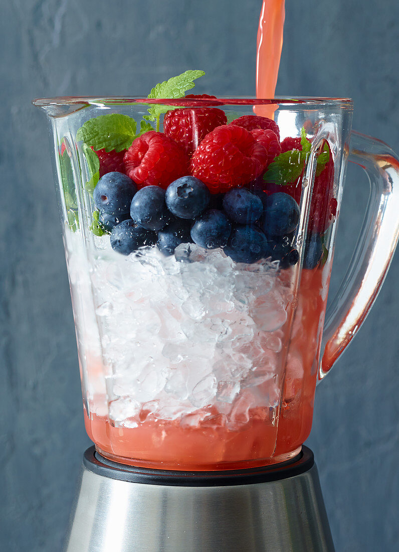 Ingredients for a berry and pomegranate slushy in a blender