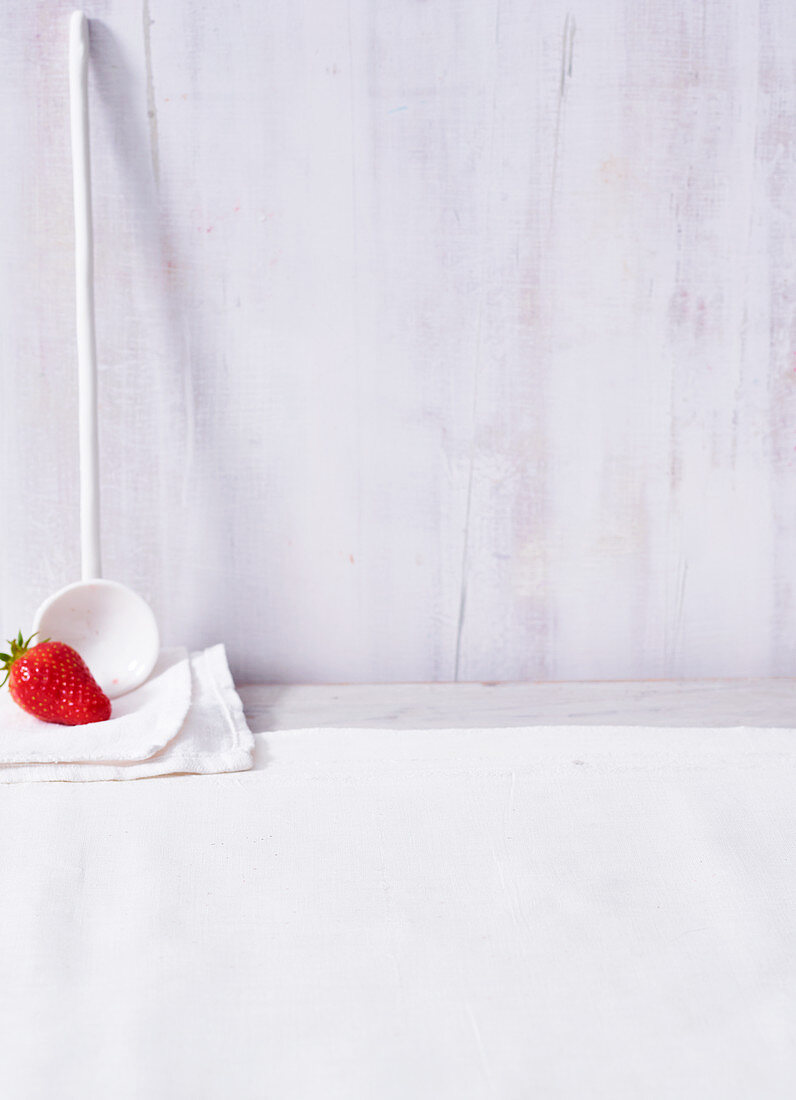 A strawberry with a white ladle, in front of a white wooden wall
