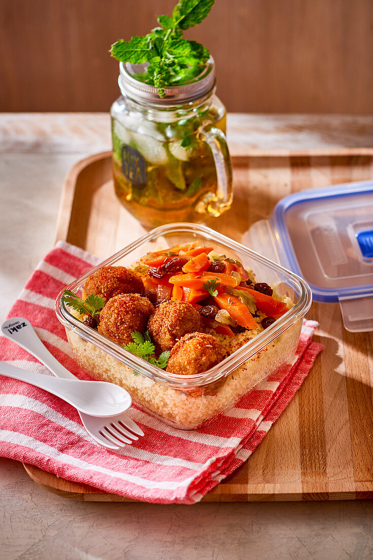 Lamb meatballs with vegetables on couscous in a tupperware box