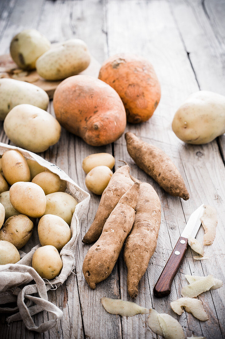 Various types of potatoes on a rustic wooden table