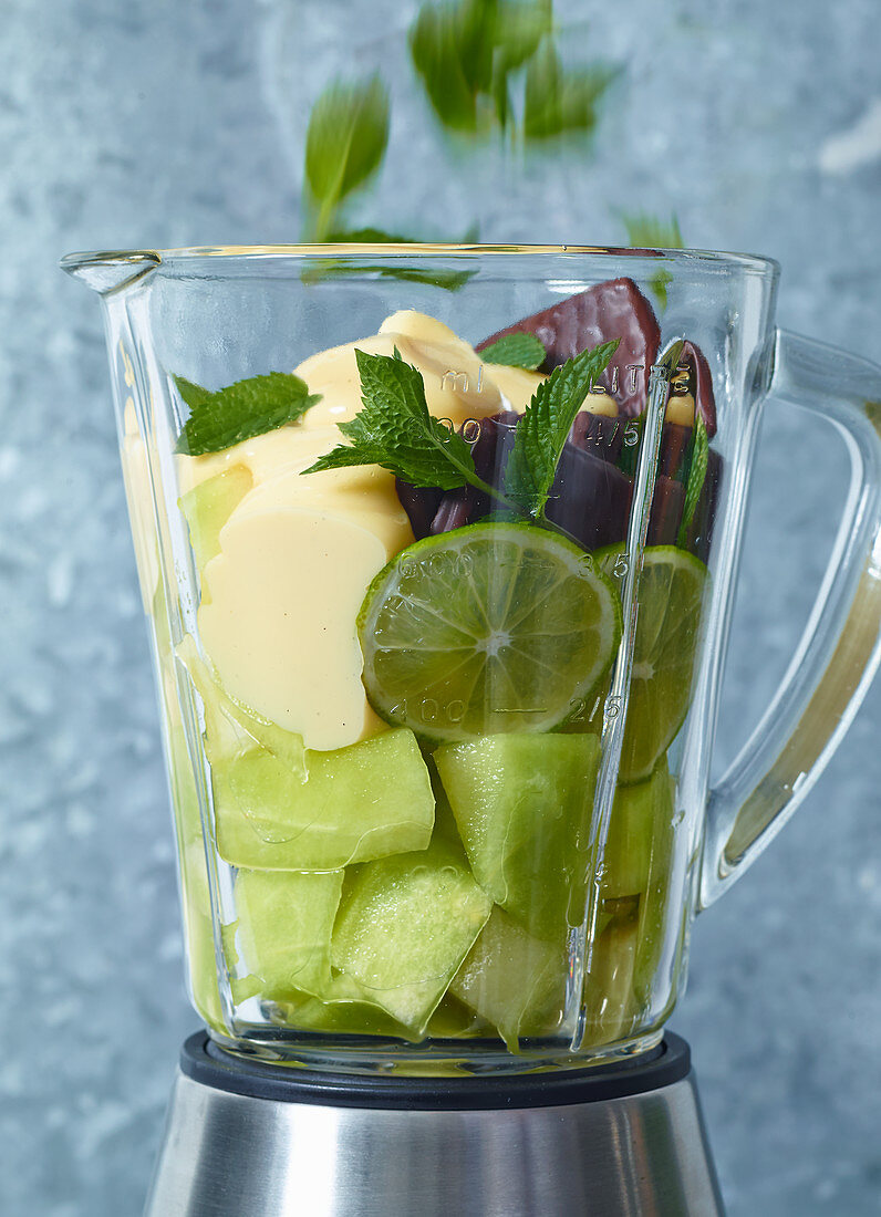 Ingredients for melon and mint cream in a blender