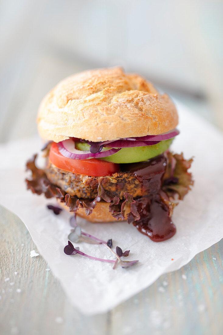 A vegan bean burger with avocado and blackberry ketchup