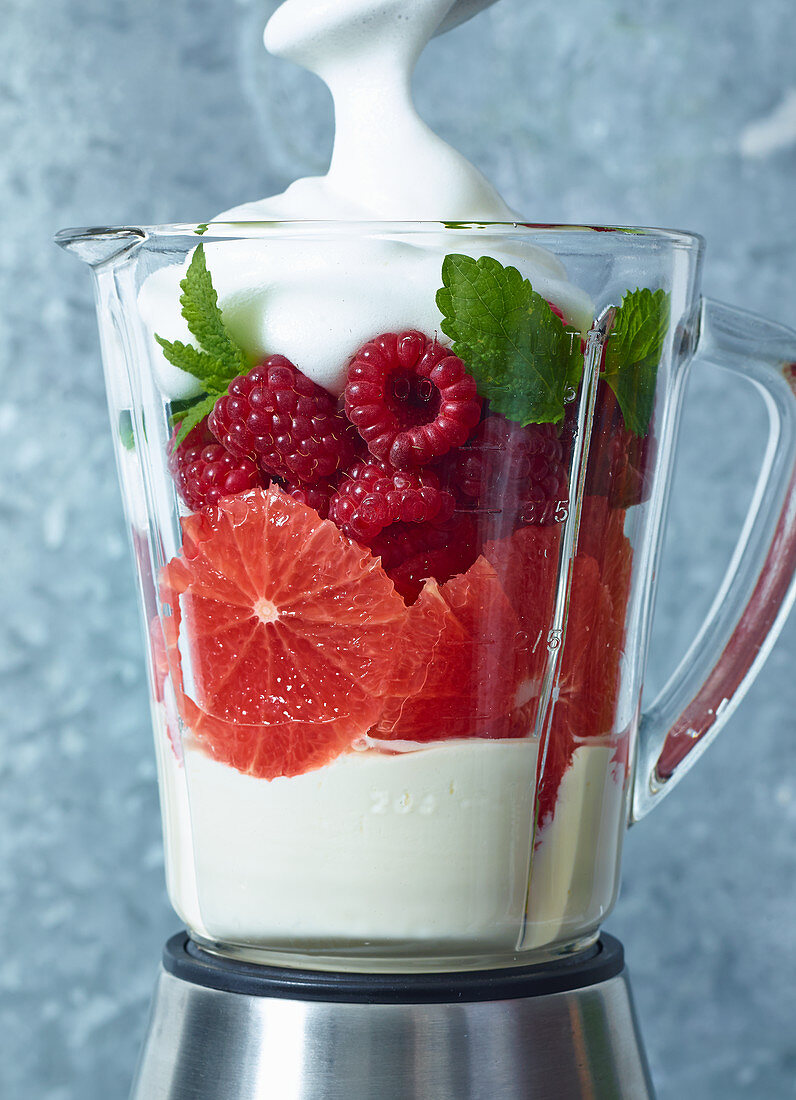 Ingredients for grapefruit and raspberry cream in a blender