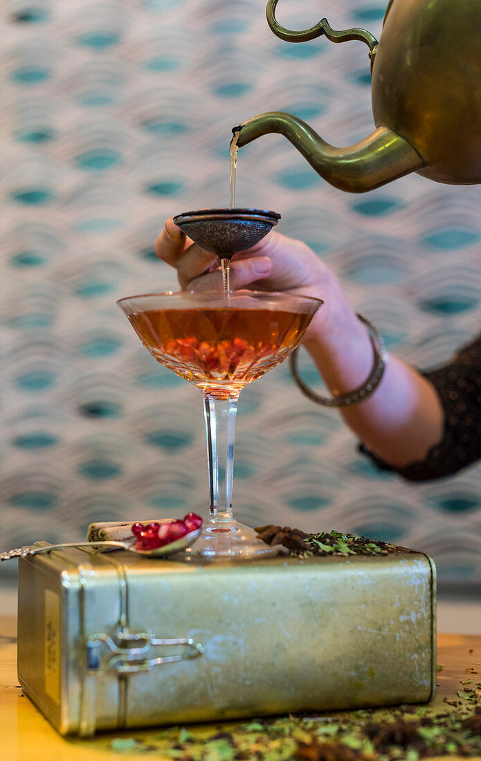 Buchu honeybush tea with gin and pomegranate seeds being poured