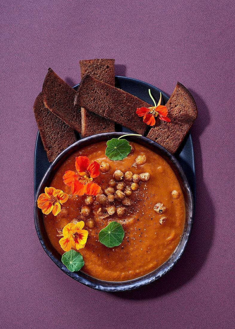 Pumpkin soup with cinnamon, sweet potatoes, mandarins and crispy chickpeas