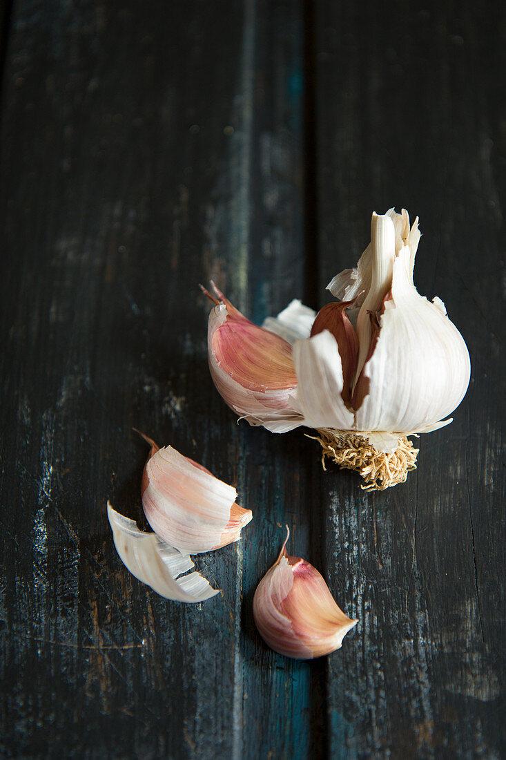A broken garlic bulb on a black wooden surface