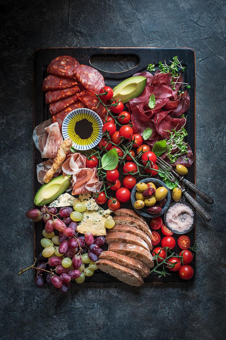 Platter with olives, cheese, parma ham, chorizo, ciabatta, grapes, avocado, olive oil, pink salt and basil