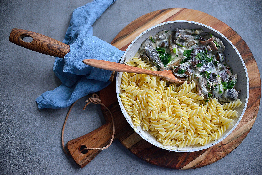 Pasta with mushrooms in a creamy sauce served in a pan (seen from above)