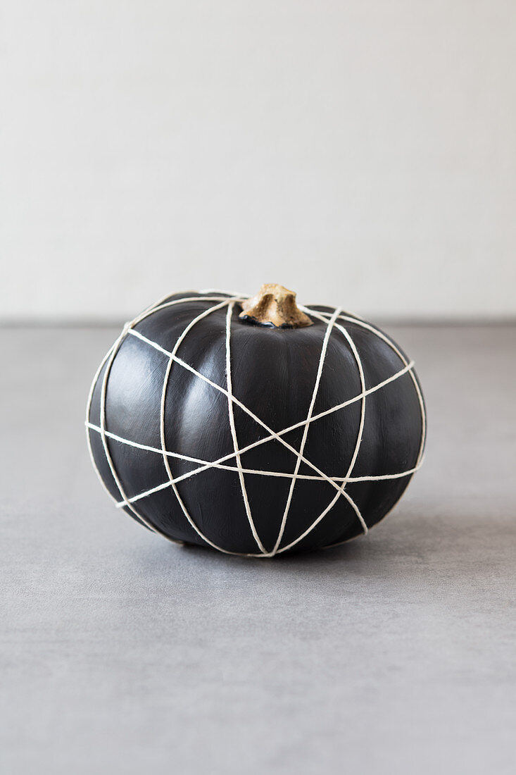 Black-painted pumpkin wrapped in criss-crossing string