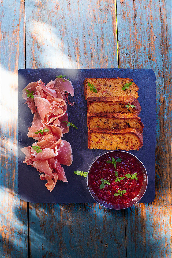 Raw ham, olive cake and a dip
