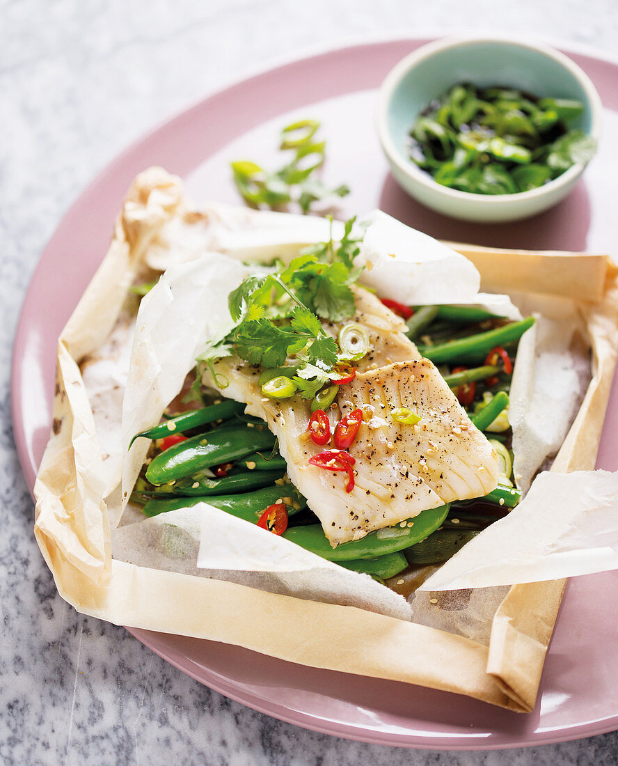 Fish fillet on green beans in parchment paper
