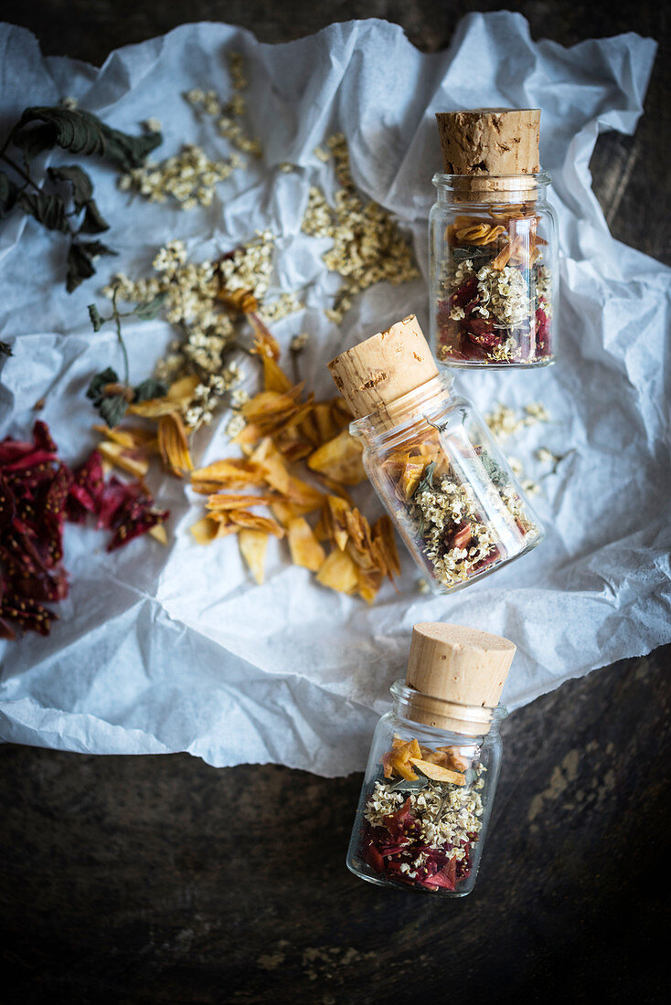 Small jars of loose leaf tea made from dried elderflowers, mint, strawberries and peach