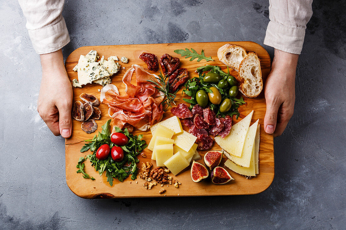 Italian snacks food with Ham, Olive, Cheese, Sun-dried tomatoes, Sausage and Bread on wooden cutting board