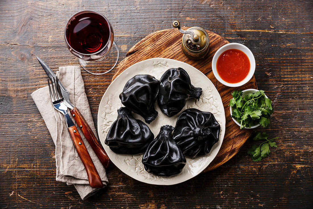 Black Georgian dumplings Khinkali with meat and tomato spicy sauce on white plate and wine