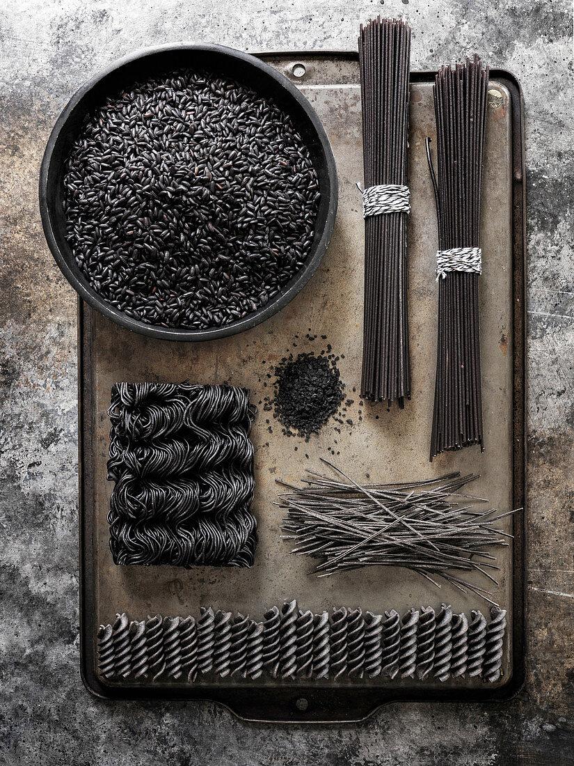 A geometric layout of black pastas (rice, spaghetti, ramen, etc…) on a dark metal surface