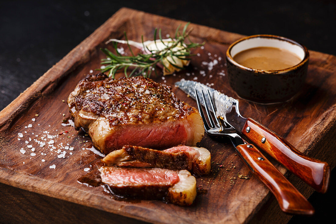 Sliced grilled meat steak (New York Striploin) with Pepper sauce and knife and fork on wooden board