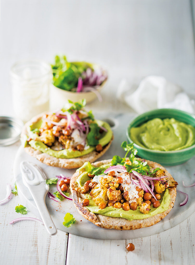 Pita breads with roasted vegetables, chickpeas and avocado cream