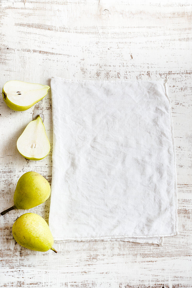 A white wooden table with a white cloth and pears